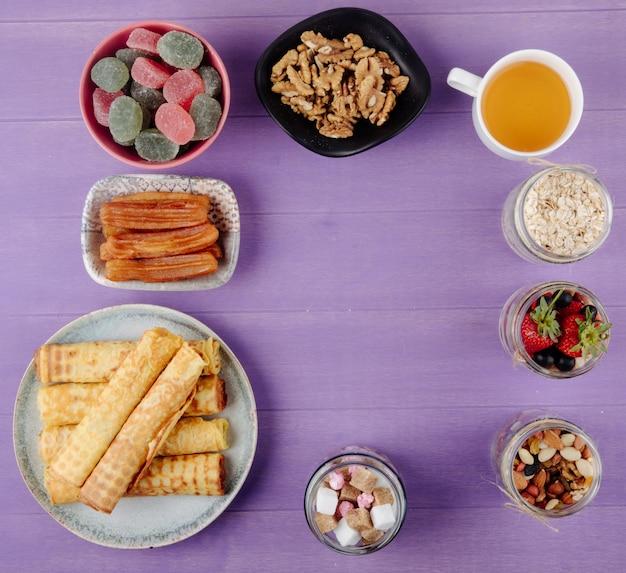 Bovenaanzicht van verschillende snoepjes voor thee en voor het ontbijt op paarse houten achtergrond