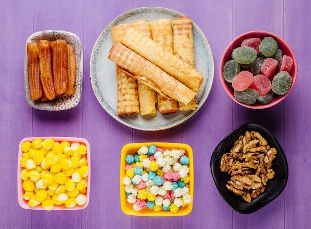 Bovenaanzicht van verschillende snoepjes voor thee snoepjes marmelade walnoten en gebak op paarse houten achtergrond