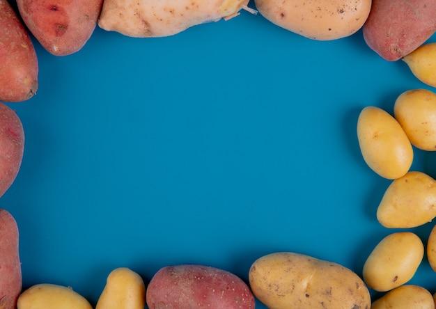 Bovenaanzicht van verschillende soorten aardappelen in ronde vorm op blauw met kopie ruimte