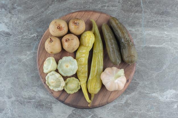 Bovenaanzicht van verschillende soorten augurk op een houten bord.