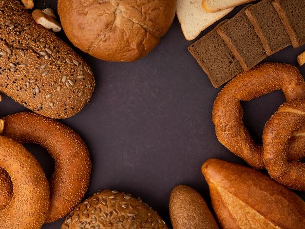 Bovenaanzicht van verschillende soorten brood als klassieke bagel en gezaaid cob rye en stokbrood stokbrood op kastanjebruine achtergrond met kopie ruimte