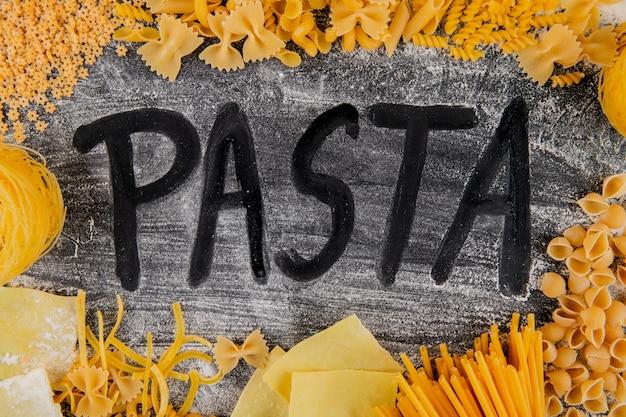 Bovenaanzicht van verschillende soorten en vormen van italiaanse pasta en woord pasta van meel op donkere achtergrond
