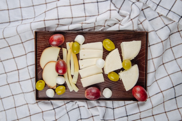 Bovenaanzicht van verschillende soorten kaas met gepekelde olijven en zoete druiven op een houten dienblad op geruite stof