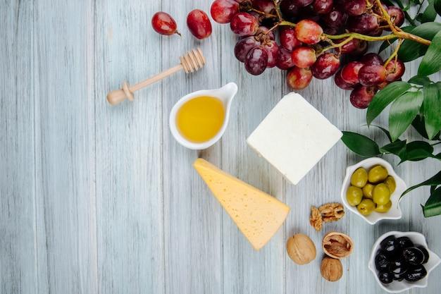 Bovenaanzicht van verschillende soorten kaas met verse druiven, honing, walnoten en gepekelde olijven op grijze houten tafel met kopie ruimte