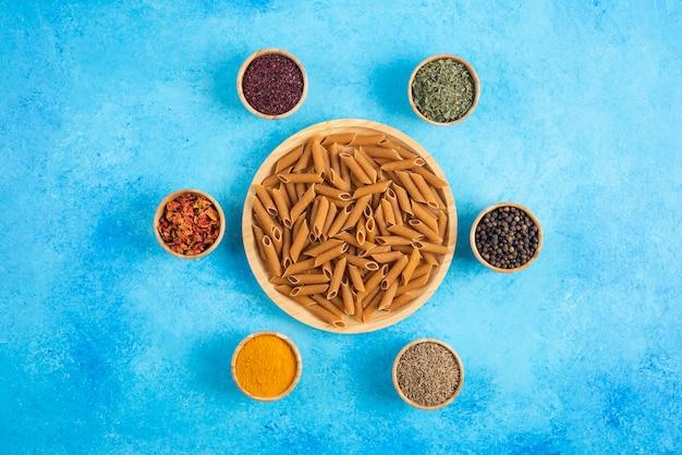 Bovenaanzicht van verschillende soorten kruiden rond bruine pasta.