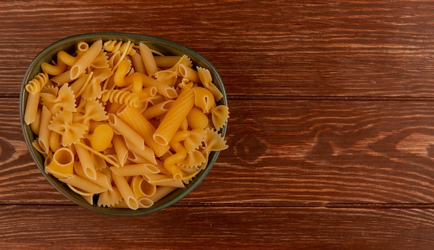 Bovenaanzicht van verschillende soorten macaroni in kom op hout met kopie ruimte
