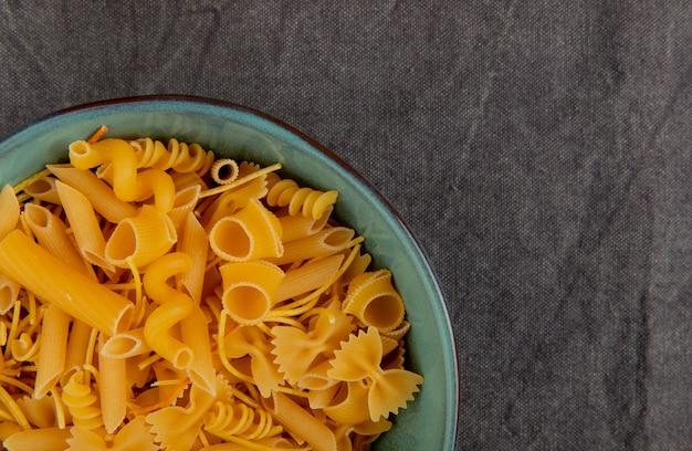 Bovenaanzicht van verschillende soorten macaroni op grijze doek met kopie ruimte