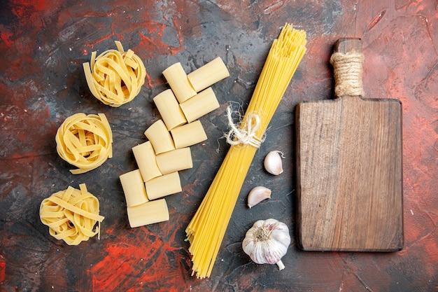 Bovenaanzicht van verschillende soorten ongekookte pasta's en houten snijplank knoflook op zwarte achtergrond