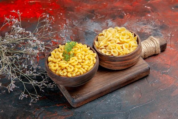 Bovenaanzicht van verschillende soorten ongekookte pasta's op houten snijplank op gemengde kleur achtergrond