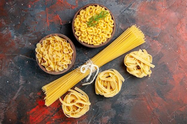 Bovenaanzicht van verschillende soorten ongekookte pasta's op tafel met gemengde kleuren