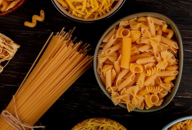 Bovenaanzicht van verschillende soorten pasta als cavatappi spaghetti vermicelli tagliatelle en anderen op houten oppervlak
