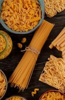 Bovenaanzicht van verschillende soorten pasta als tagliatelle spaghetti vermicelli en anderen op houten oppervlak