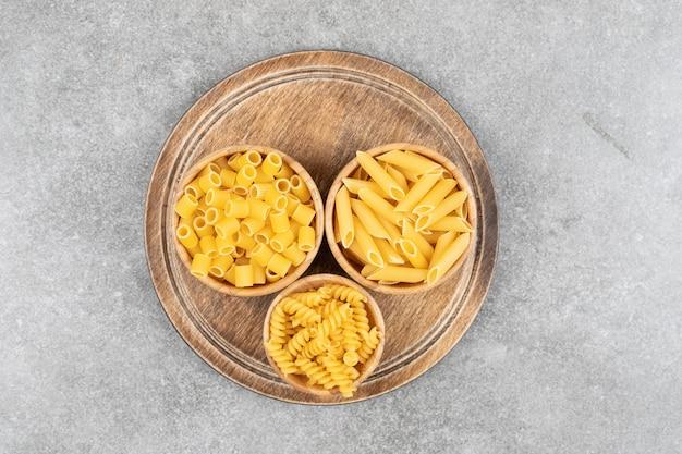 Bovenaanzicht van verschillende soorten pasta in kommen over houten bord
