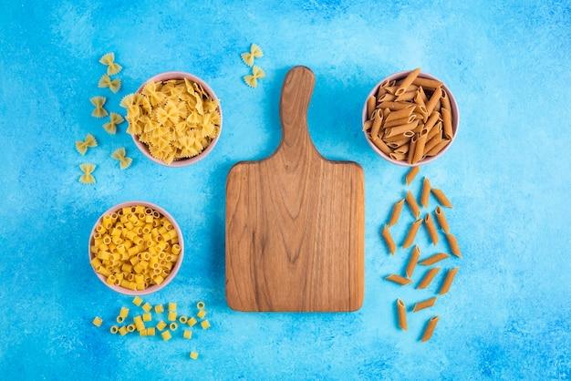Bovenaanzicht van verschillende soorten pasta op blauwe tafel.