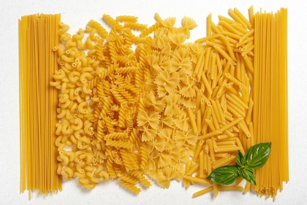 Bovenaanzicht van verschillende soorten pasta op effen achtergrond