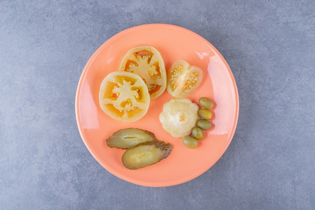 Bovenaanzicht van verschillende soorten plantaardige augurk op oranje plaat.