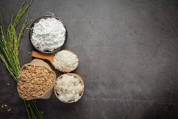 Bovenaanzicht van verschillende soorten producten van rijst op donkere vloer