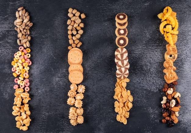 Bovenaanzicht van verschillende soorten snacks als noten, crackers en koekjes met kopie ruimte op donkere horizontale oppervlak