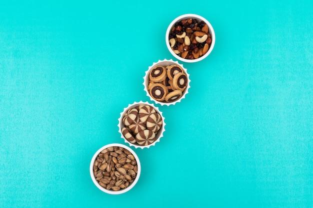Bovenaanzicht van verschillende soorten snacks als noten en coockies in kommen op blauwe horizontaal