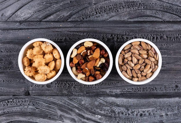Bovenaanzicht van verschillende soorten snacks als noten en crackers in kommen op donkere horizontaal