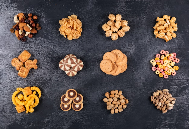 Bovenaanzicht van verschillende soorten snacks zoals noten, crackers en coockies op donkere horizontale