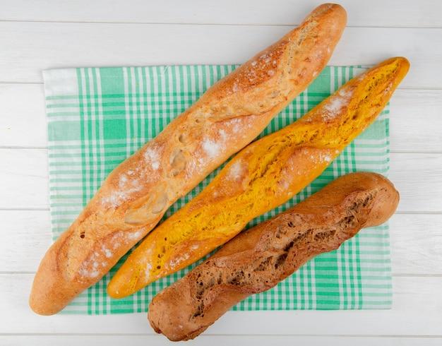Bovenaanzicht van verschillende soorten stokbrood op geruite doek en houten tafel