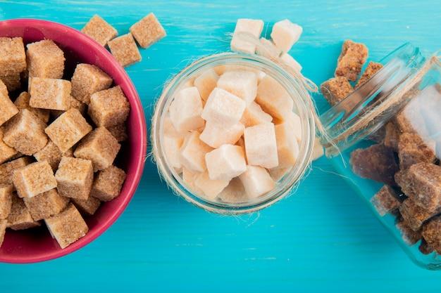 Bovenaanzicht van verschillende soorten suiker in glazen potten op blauwe houten achtergrond