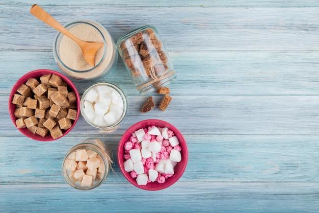 Bovenaanzicht van verschillende soorten suiker in glazen potten op rustieke achtergrond met kopie ruimte