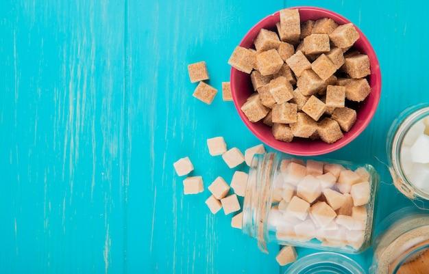 Bovenaanzicht van verschillende soorten suiker in kommen en in glazen potten op blauwe houten achtergrond met kopie ruimte