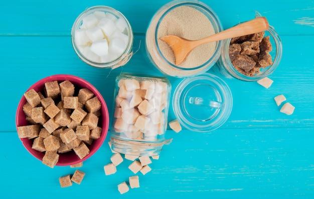 Bovenaanzicht van verschillende soorten suiker in kommen en in glazen potten op blauwe houten achtergrond