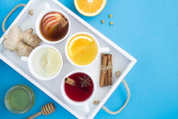 Bovenaanzicht van verschillende soorten thee in de witte kopjes in het houten dienblad op de blauwe achtergrond