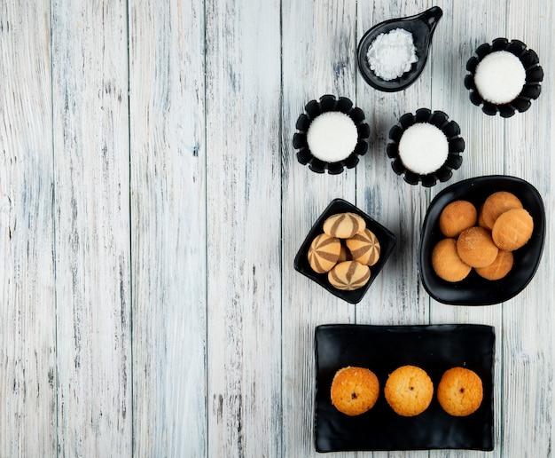 Bovenaanzicht van verschillende soorten zoete koekjes en muffins op zwarte dienbladen op houten achtergrond met kopie ruimte