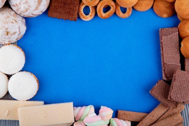Bovenaanzicht van verschillende soorten zoete koekjes marshmallows en brood ringen gerangschikt in een vorm van frame op blauwe achtergrond met kopie ruimte