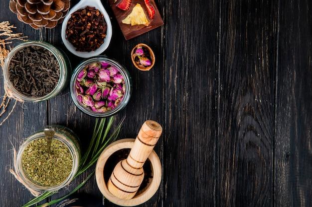 Bovenaanzicht van verschillende specerijen en kruiden droge zwarte theebladeren, pepermunt, rozenknoppen, kruidnagel en zwarte peper in glazen potten op zwart hout met kopie ruimte