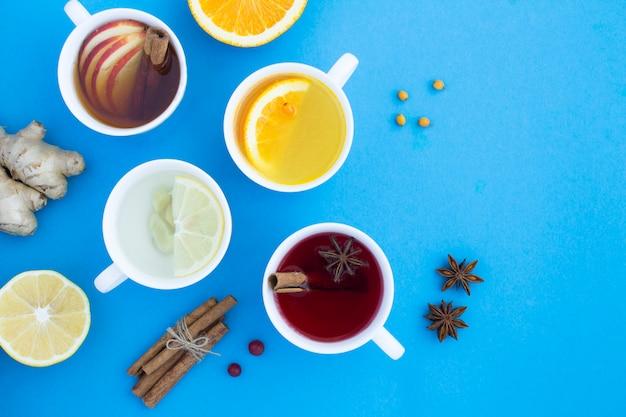 Bovenaanzicht van verschillende theeën in de witte kopjes op de blauwe achtergrond