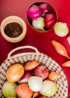 Bovenaanzicht van verschillende uien in mand met andere in kom en zwarte peper zaden op rood