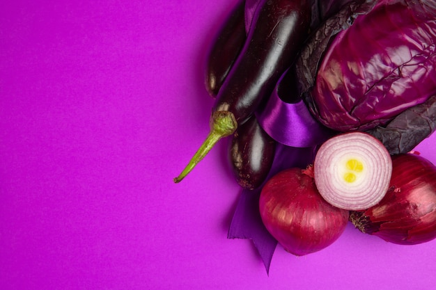 Bovenaanzicht van verschillende verse groenten aubergines rode ui en kool op paars