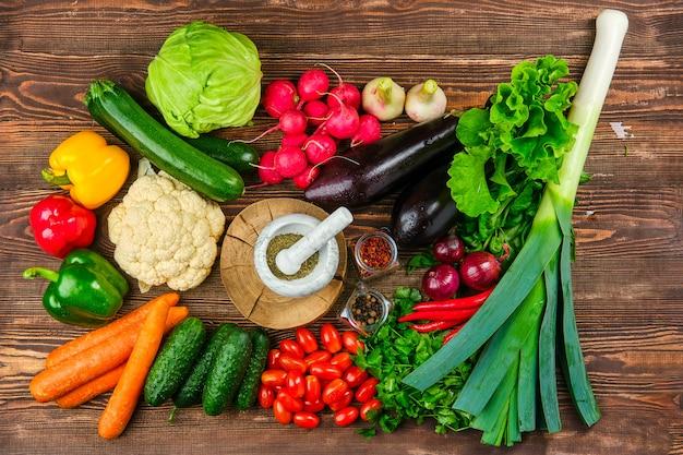 Bovenaanzicht van verschillende verse groenten en kruiden op donkere houten muur