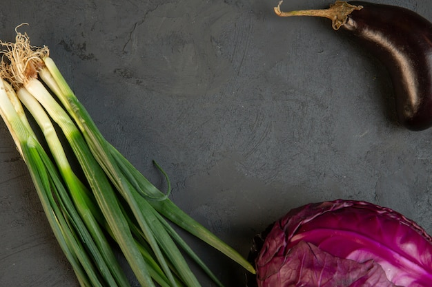 Bovenaanzicht van verschillende verse groenten rode kool aubergine en groene ui met kopie ruimte op donkere j