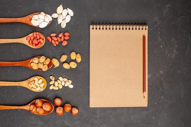Bovenaanzicht van verschillende verse noten, pinda's en andere noten op donkere ondergrond