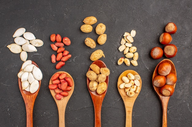 Bovenaanzicht van verschillende verse noten, pinda's en andere noten op lepels op donkere ondergrond Gratis Foto