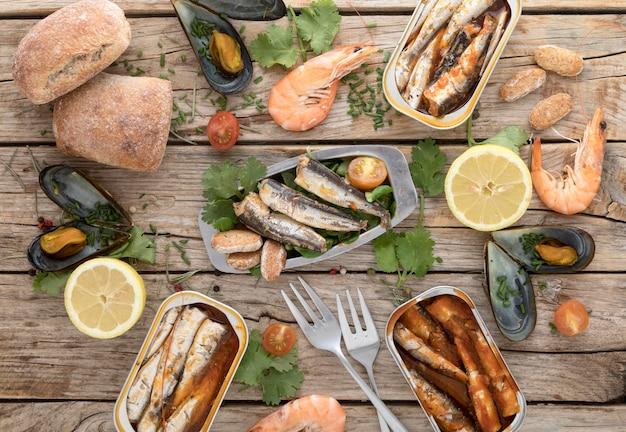 Bovenaanzicht van verschillende visgerechten met bestek en citroen