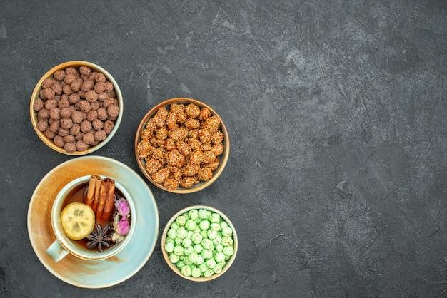 Bovenaanzicht van verschillende zoete snoepjes met kopje thee op grijs