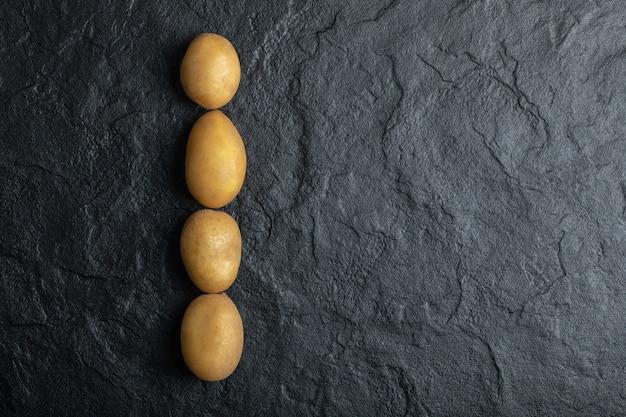 Bovenaanzicht van verse aardappelen op een rij op zwarte stenen achtergrond.