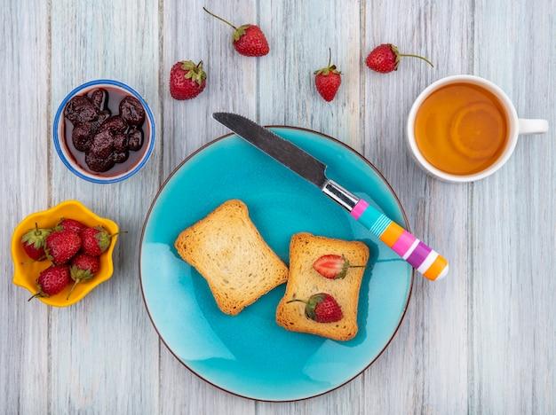 Bovenaanzicht van verse aardbeien op een geroosterd brood op een blauw bord met mes met een aardbeienjam met verse aardbeien met een kopje thee op een grijze houten achtergrond