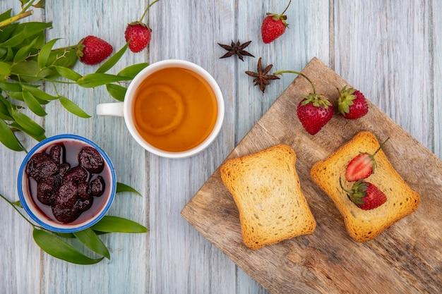 Bovenaanzicht van verse aardbeien op een houten keukenbord met geroosterde sneetjes brood met een aardbeienjam met een kopje thee op een grijze een houten achtergrond