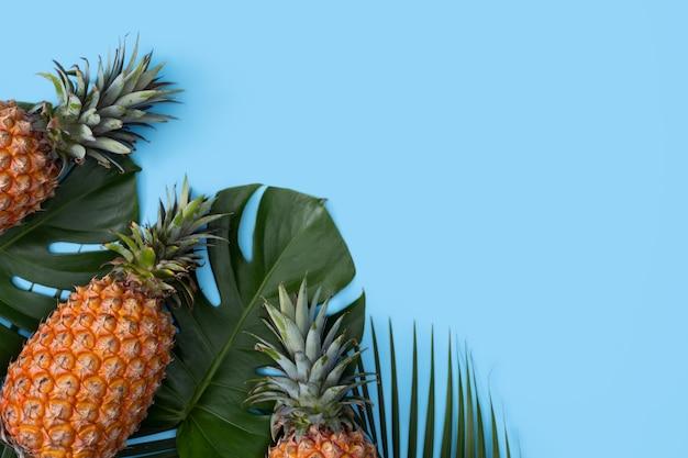 Bovenaanzicht van verse ananas met tropische palm en monsterabladeren op blauwe tafelachtergrond.