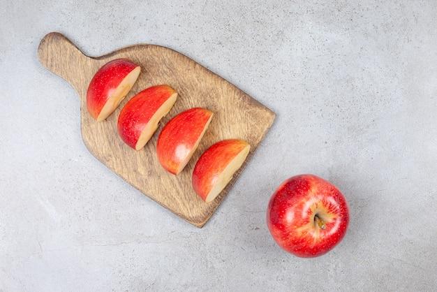 Bovenaanzicht van verse appelschijfjes op houten snijplank en hele appel op grijs oppervlak.