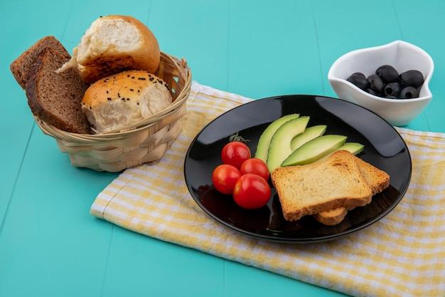 Bovenaanzicht van verse avocado plakjes met tomaten en geroosterde sneetjes brood op zwarte plaat op geel gecontroleerd tafellaken met zwarte olijven op witte kom op blauw