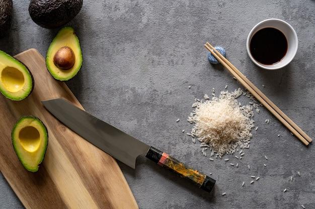 Bovenaanzicht van verse avocado's, een snijplank en mes, rijst en eetstokjes op een grijze ondergrond